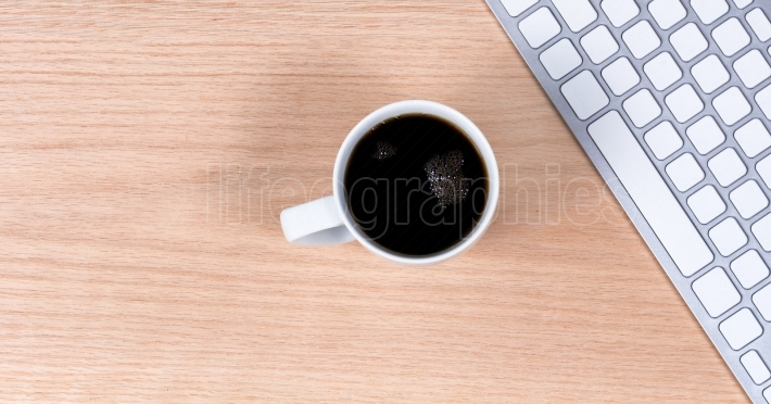 Dark coffee with keyboard on red oak desktop background
