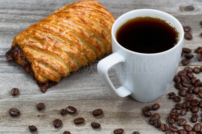 Dark coffee with large pastry on rustic wood