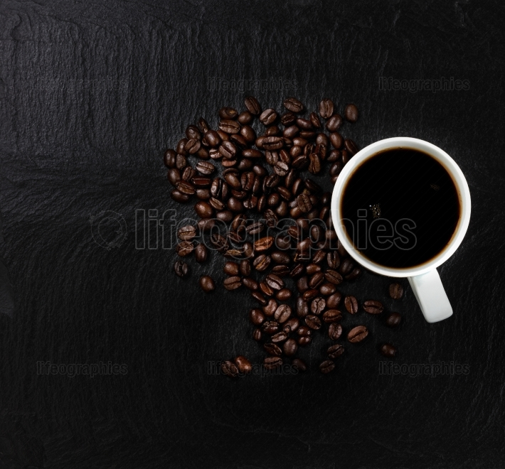 Dark coffee with roasted beans on natural slate stone background