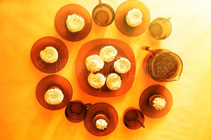 Decorated table with fresh cupcakes warm background