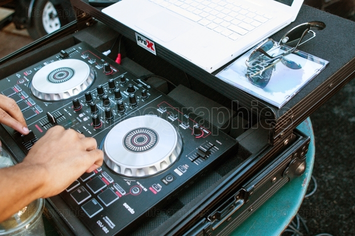 Deejay turns knobs on sound equipment at hip hop festival