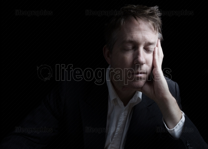 Depressed man resting his eyes