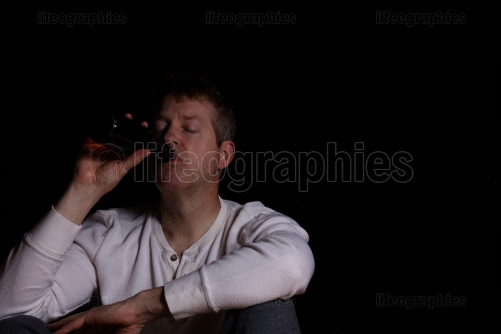 Depressed mature man drinking a beer in dark background