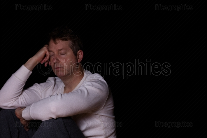 Depressed mature man thinking with his eyes closed in dark backg