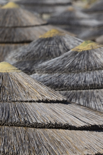 Detail of woven umbrellas above rows on beach in cyprus