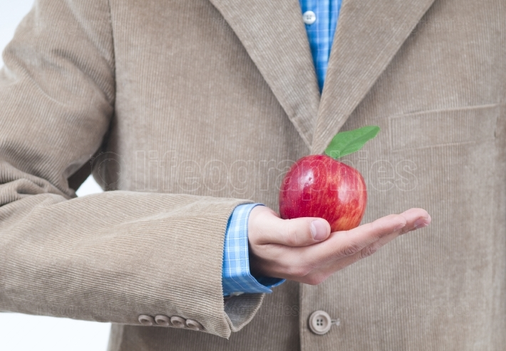 Detailed business man hand holding a red apple.