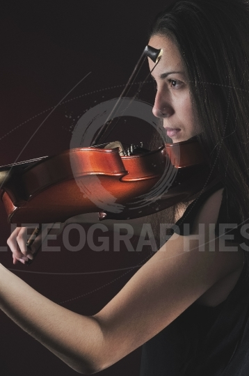 Detailed picture with a beautiful young woman playing a violin