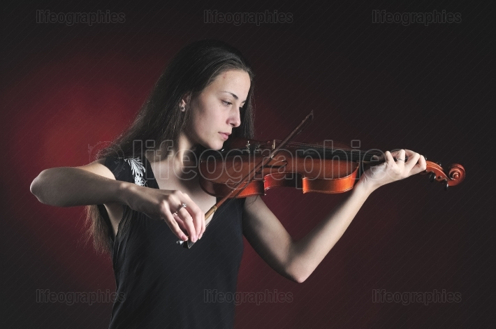 Detailed picture with a beautiful young woman playing a violin over black background