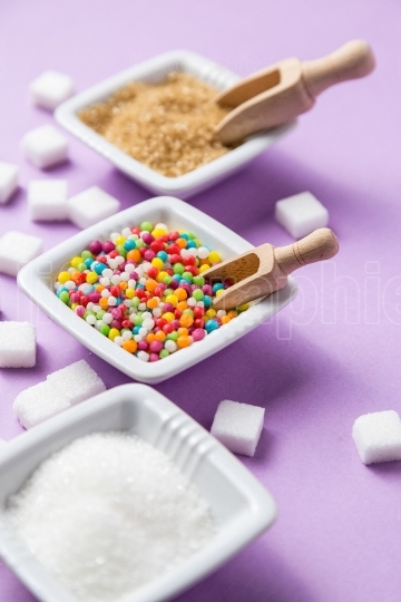 Different types of sugar with colored candy on  ceramic bowls