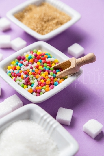 Different types of sugar with colored candy on white ceramic bow