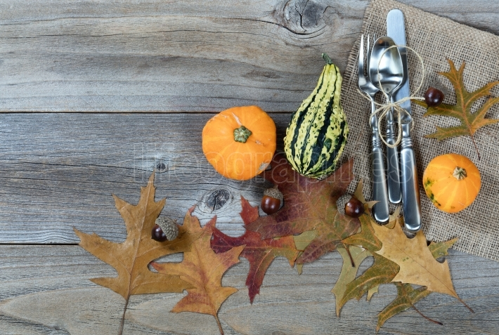 Dinner setting for fall Thanksgiving holiday on rustic wooden bo
