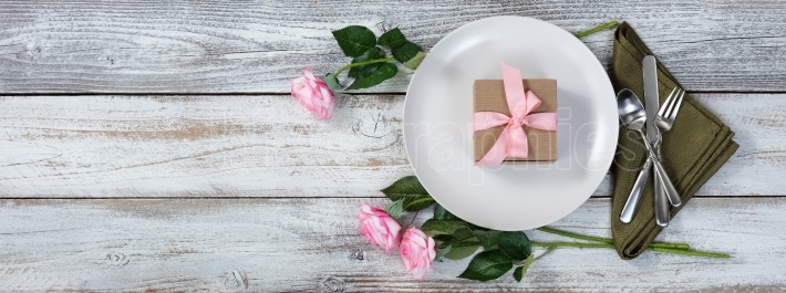 Dinner setting with pink roses and gift on rustic white wood