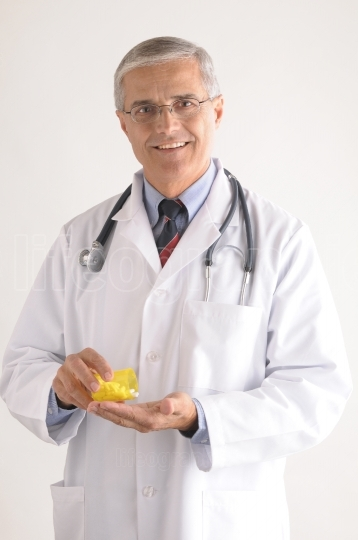 Doctor in Labcoat Pouring Pills into Hand