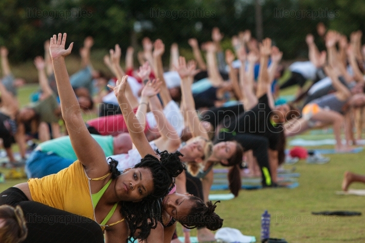 Dozens Of People Do Triangle Pose At Outdoor Yoga Class