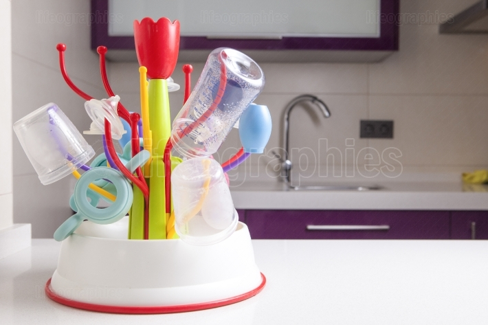 Drainer full of baby plastic tableware objects