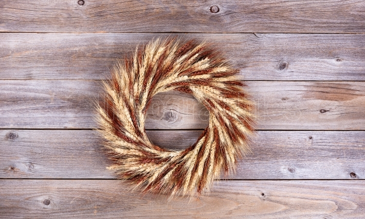Dried wheat stalk wreath on rustic wooden boards