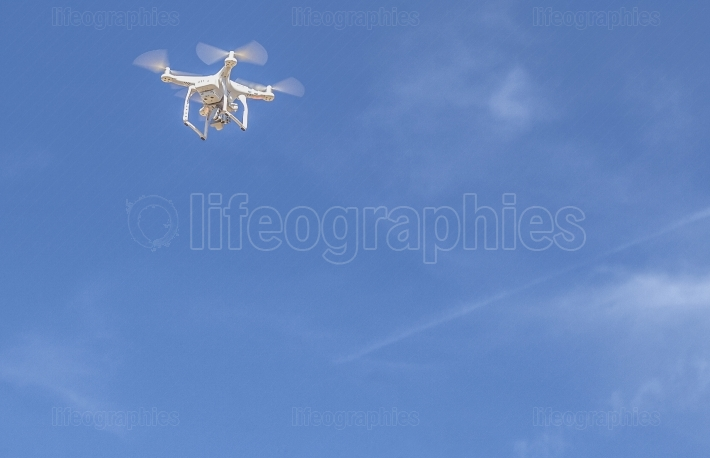 Drone flying over with camera against blue sky