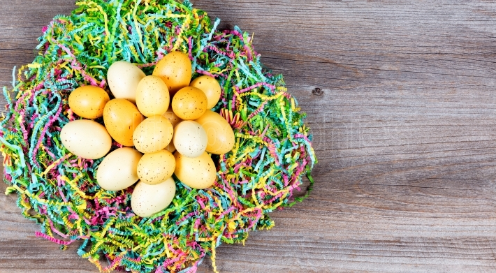 Easter eggs on top of colorful Mache paper with rustic wooden bo