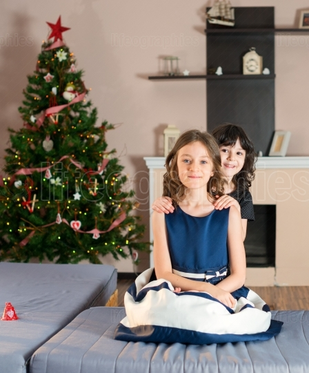 Elder sister with the younger one. Girls sitting on the couch near a Christmas tree and presents.