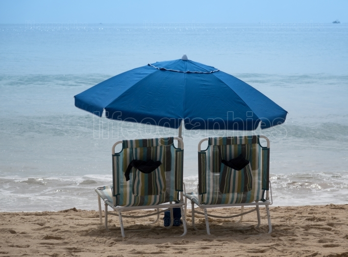 Empty beach chairs with umbrellas on sandy beach of Pacific Ocea