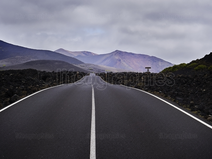 Empty endless highway through the volcanic landscape of Lanzarot