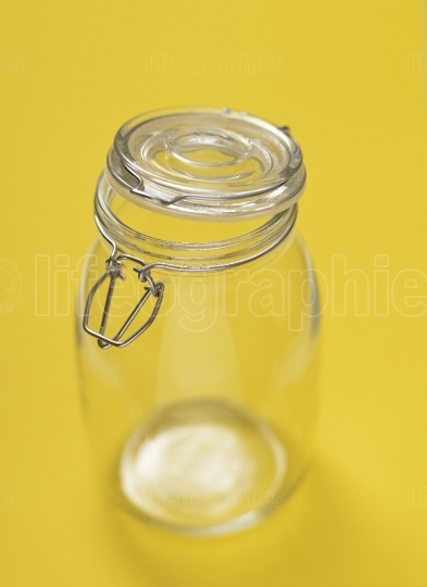 Empty glass jar isolated on a yellow background