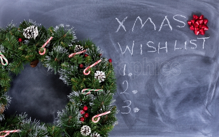 Erased black chalkboard with holiday wreath plus text writing