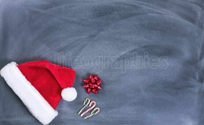 Erased black chalkboard with Santa cap and candy canes plus gift