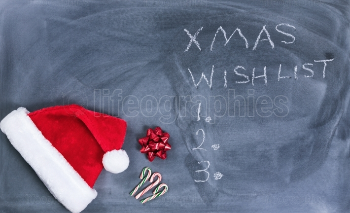 Erased black chalkboard with Santa cap and candy canes plus text