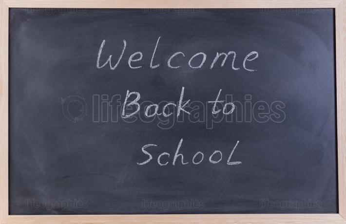 Erased black chalkboard with welcome back to school message for
