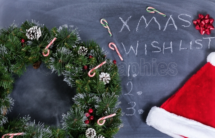 Erased black chalkboard with wreath and other Xmas items plus te