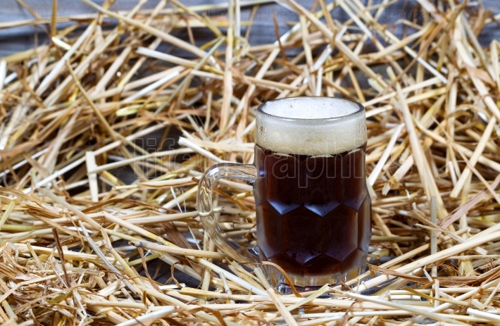 European Dark Beer in Stein on Straw and wood