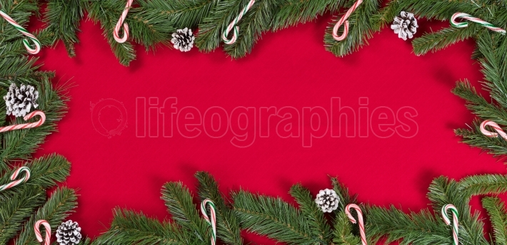 Evergreen branches and candy canes forming border on bright red