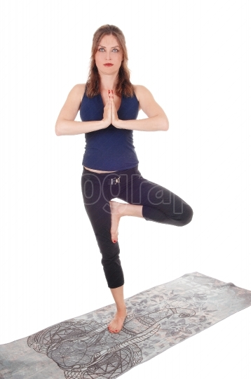 Exercising woman standing on one leg