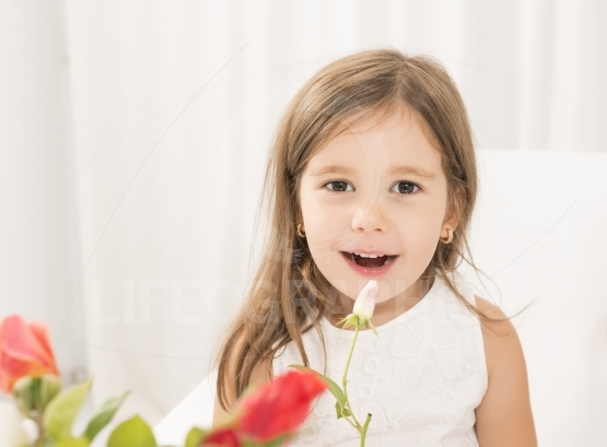 Exprecive little girl with roses