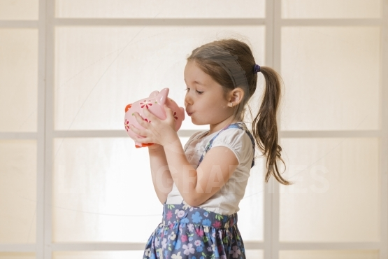 Expressive  little girl kissing pink piggy bank