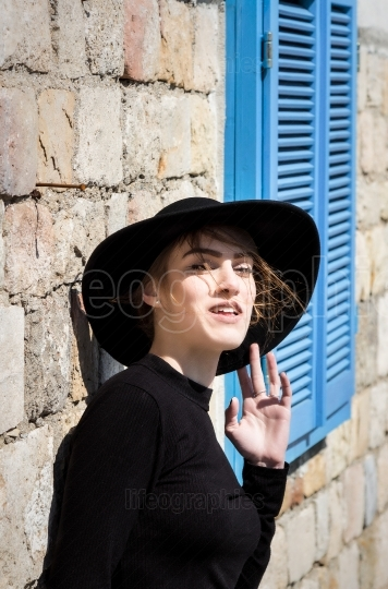 Expressive beautiful young woman in black with black hat looking
