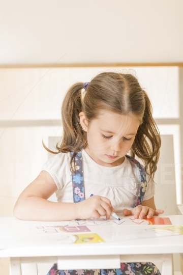Expressive little child writing letter A