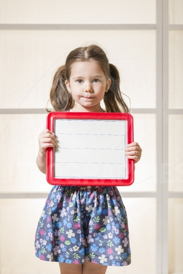 Expressive little girl holding a blank magnetic board