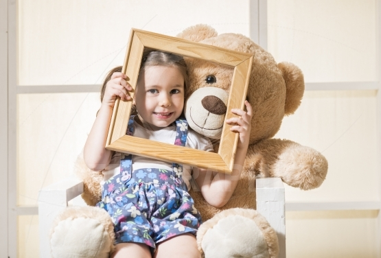 Expressive little girl holding an empty frame posing with her toy friend