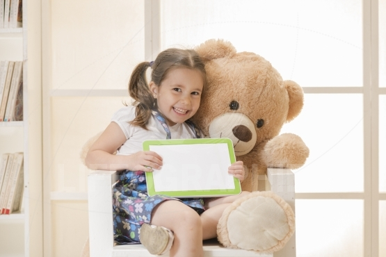 Expressive little girl sitting in Teddy bear arms showing her tablet computer