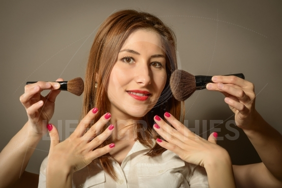 Expressive young woman feeling pretty, getting make-up applied
