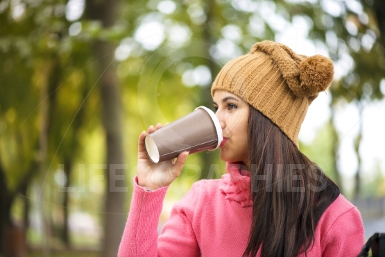 Fall concept - autumn woman drinking coffee on park bench under fall foliage.
