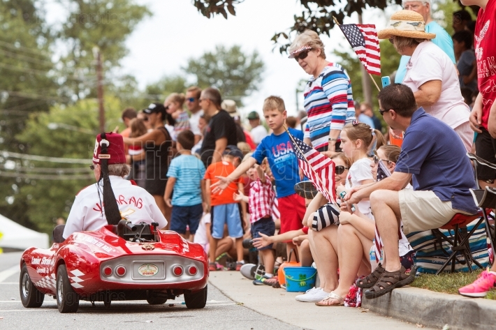Families Wave American Flags At Old Soldiers Day Parade