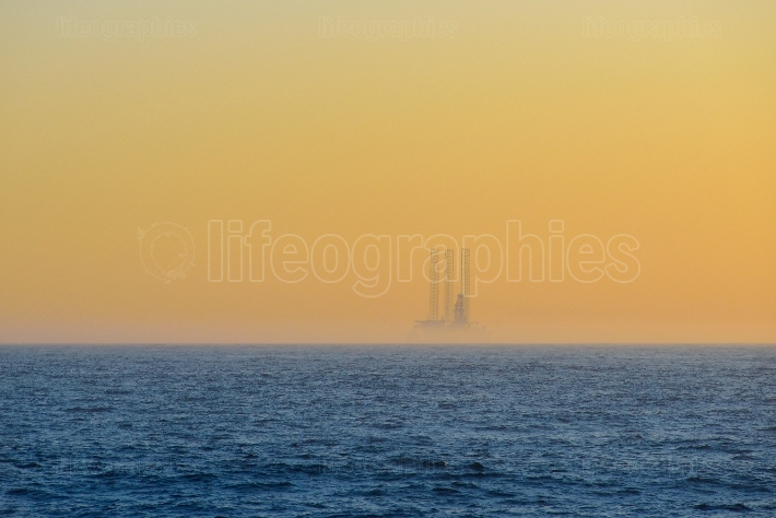 Far away oil platform at sunrise