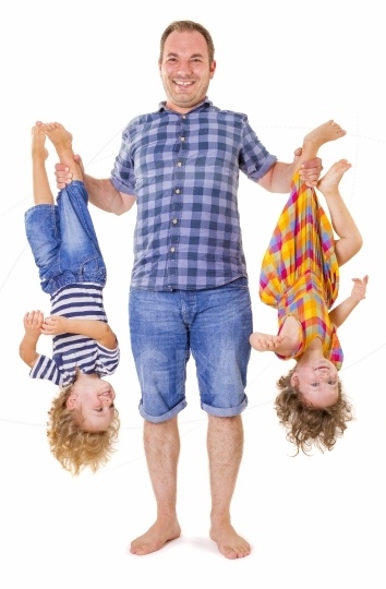 Father holding his smiling children upside down