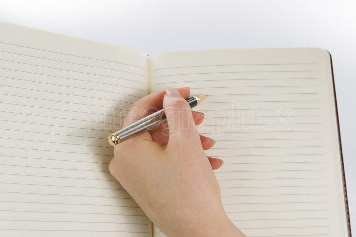 Female hand ready to write with pen and paper