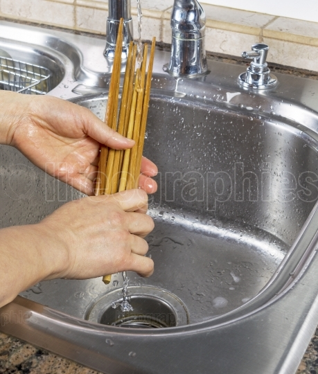 Female hands rinsing off bamboo chopsticks