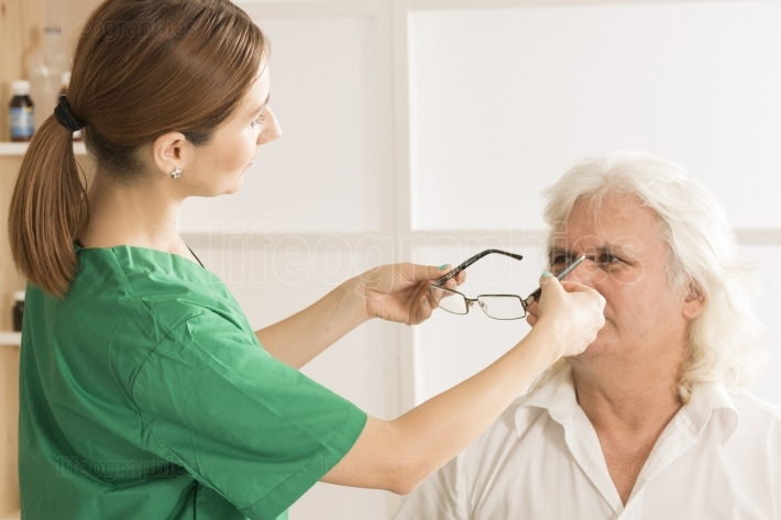 Female optometrist and elderly man patient in ophthalmology clinic