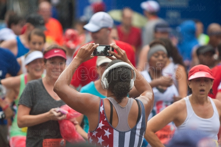 Female runner takes picture of finish line with smartphone